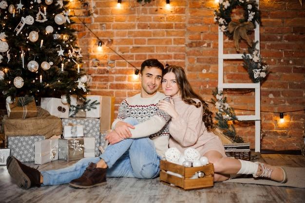 Mulher grávida com o marido sentado perto da árvore de natal e caixas de presente