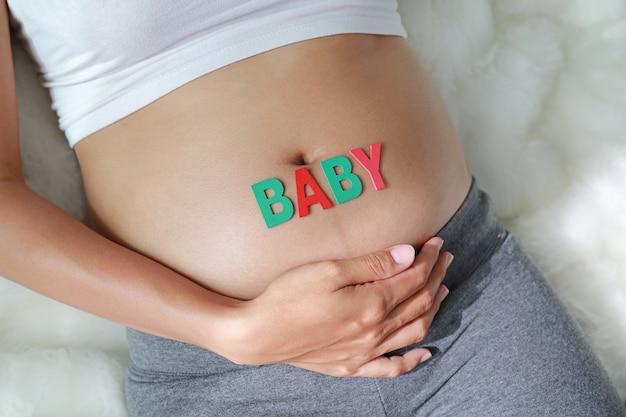 Mulher grávida, com, palavra bebê, frente, dela, barriga
