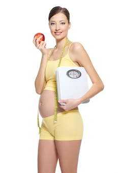 Mulher grávida com roupas esportivas amarelas segurando uma maçã vermelha e balanças brancas
