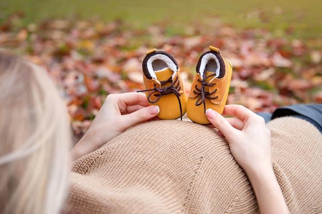 Mulher grávida com sapatos de bebê fofos no parque outono, close up