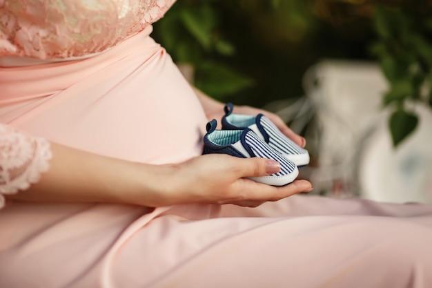 Mulher grávida com sapatos infantis nas mãos, maternidade, jovem mãe esperando bebê