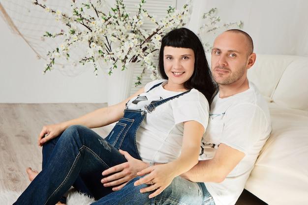 Mulher grávida com seu marido amoroso em uma feliz antecipação do bebê