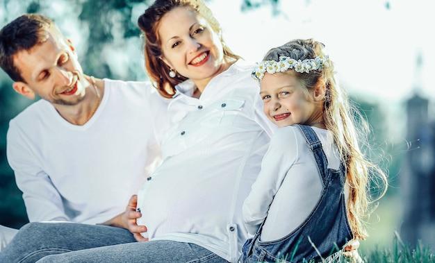 Mulher grávida com sorte, pai e filha, sentados na grama do parque em um dia ensolarado