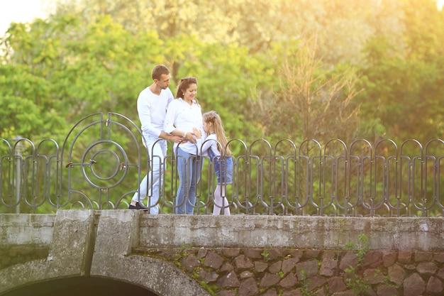 Mulher grávida com sua filha e marido em uma caminhada
