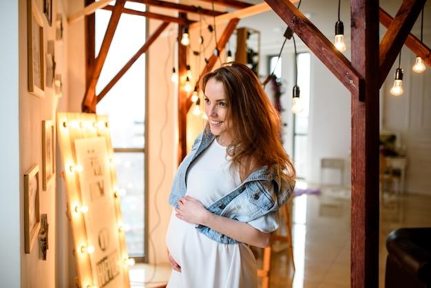 Mulher grávida com tatuagem em um vestido branco