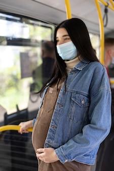 Mulher grávida com tiro médio usando máscara