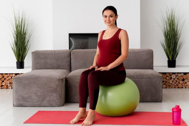 Mulher grávida com um tiro certeiro sentado em uma bola de fitness