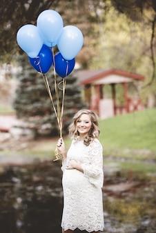 Mulher grávida com um vestido branco segurando balões em um jardim sob a luz do sol