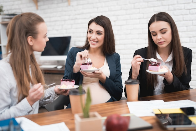 Mulher grávida, comendo bolo, com, colegas, escritório