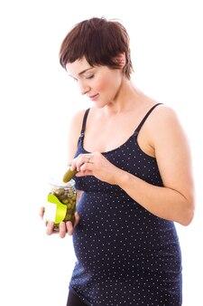 Mulher grávida comendo jarra de picles