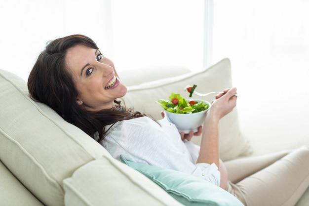 Mulher grávida, comendo salada, ligado, sofá