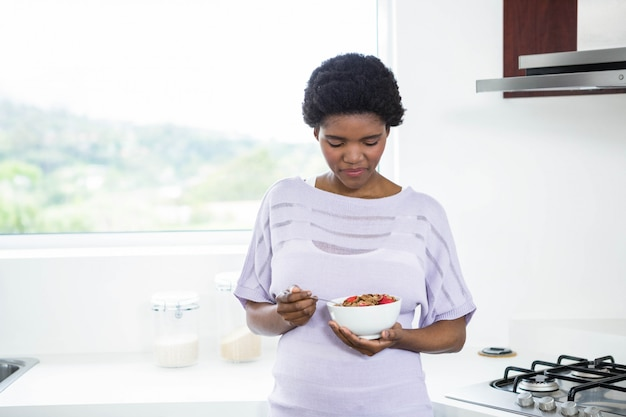Mulher grávida, comer, cereal, em, cozinha