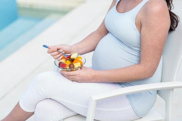 Mulher grávida, comer, fruta, perto, piscina