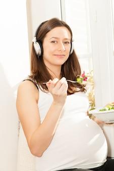 Mulher grávida comer salada e ouvir música