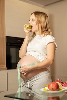 Mulher grávida comer uma maçã e medir a barriga