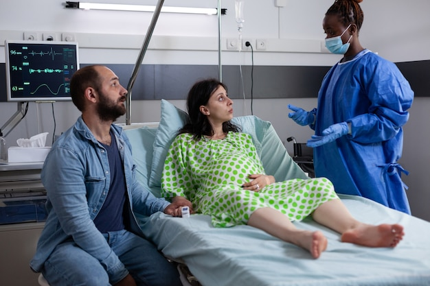 Mulher grávida conversando com enfermeira obstétrica