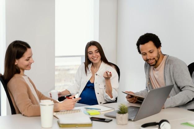 Mulher grávida conversando com seu colega de trabalho