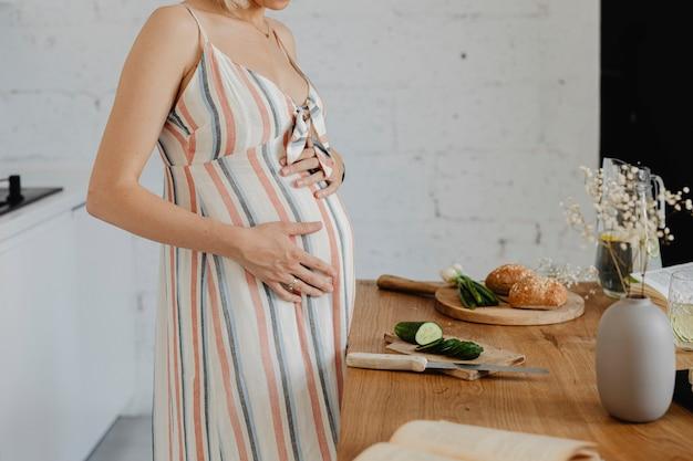 Mulher grávida cozinhando em uma cozinha