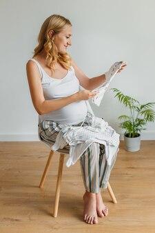 Mulher grávida cuidando das roupas do bebê. feliz futura mãe se preparando durante a gravidez