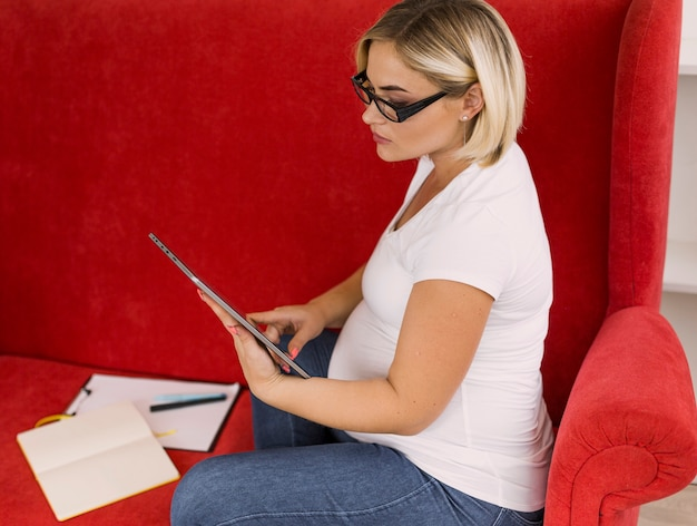 Mulher gravida de alto ângulo, olhando para o tablet