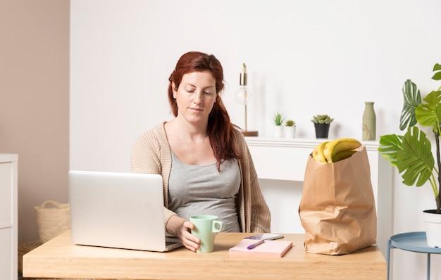 Mulher gravida de baixo ângulo em casa