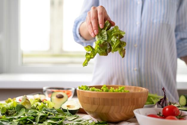 Mulher grávida de camisa azul prepara salada de vegetais de espinafre, abacate, tomate cereja, joga folhas de alface em uma tigela de madeira, espaço de cópia, efeito de movimento