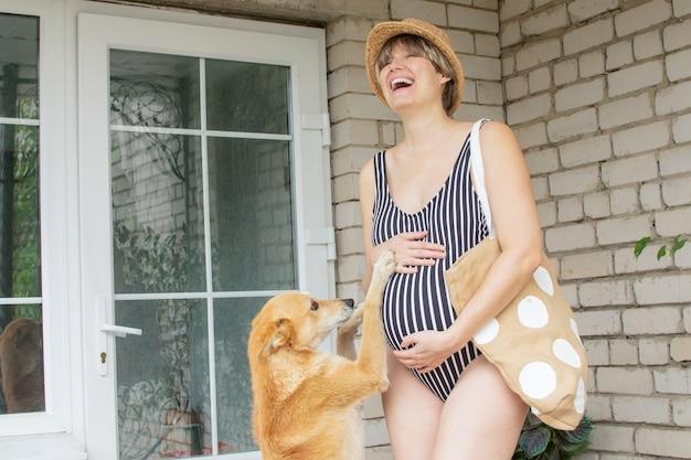 Mulher grávida de maiô brinca com um cachorro saindo de casa para passear, gravidez saudável.