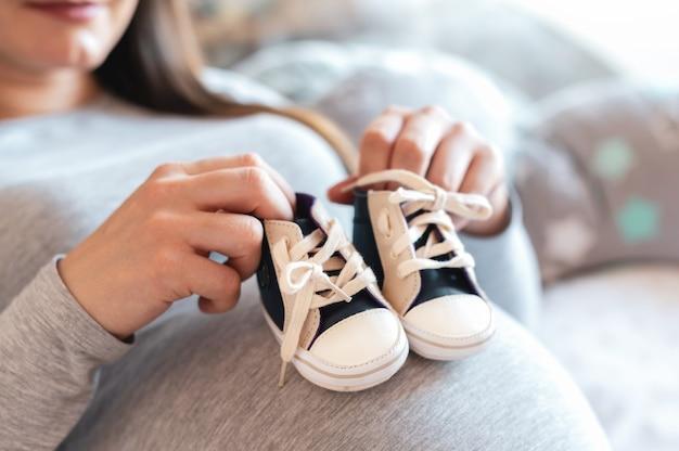 Mulher grávida deitada na cama segurando sapatinhos na barriga