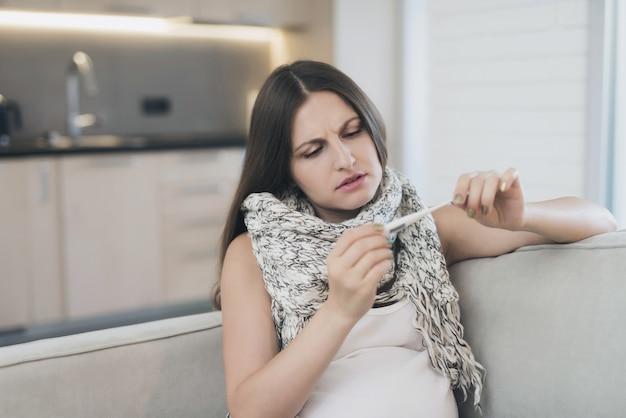 Mulher gravida doente que senta-se em casa no sofá.