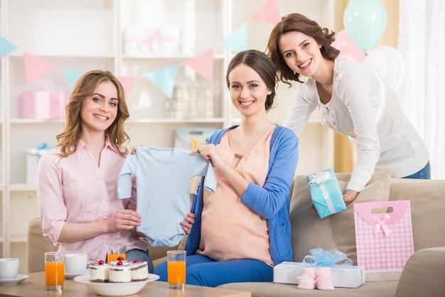 Mulher grávida é abrir um novo presente no chá de bebê.