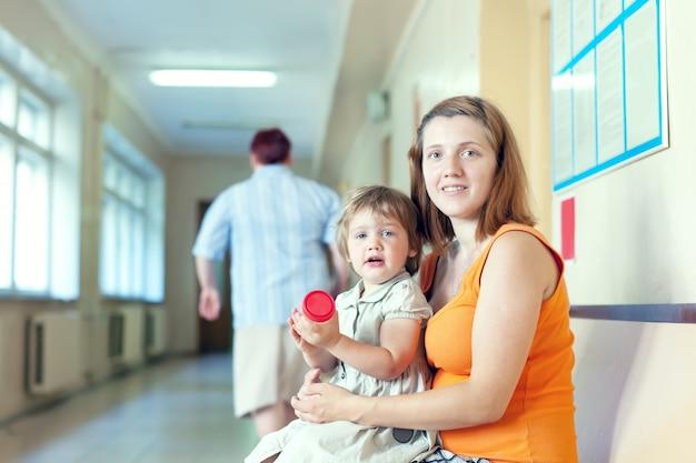 Mulher grávida e criança com amostra de análise de urina