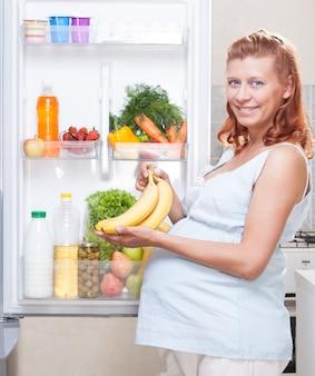 Mulher grávida e geladeira com vegetais e frutas saudáveis