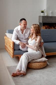 Mulher grávida e homem rindo lindo casal jovem sentado e conversando dentro de casa em casa