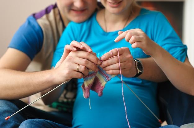 Mulher grávida e marido tricô