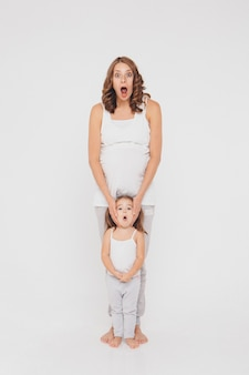 Mulher grávida e menina no sportswear