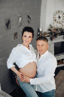 Mulher grávida e o marido com camisas brancas combinando se abraçando