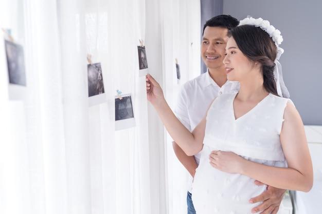 Mulher grávida e o marido olhando foto de varredura de ultra-som na janela