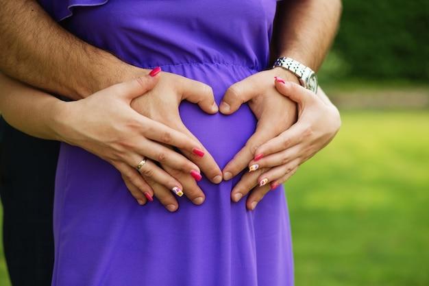 Mulher grávida e seu marido segurando as mãos em forma de coração na barriga dela