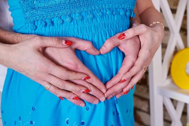 Mulher grávida e seu marido segurando as mãos em forma de coração Foto Premium
