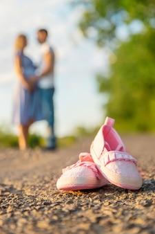 Mulher grávida e um homem com sapatos de bebê
