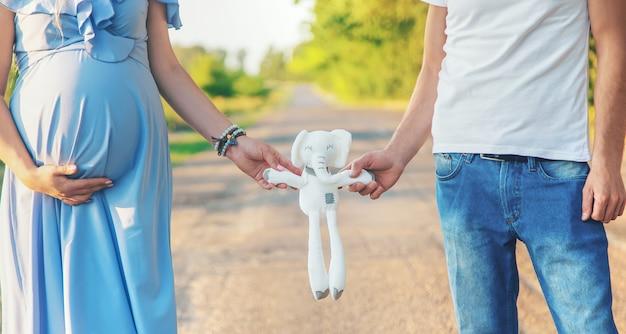 Mulher grávida e um homem segurando um brinquedo