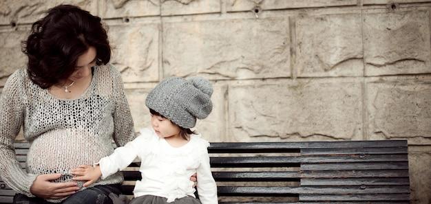 Mulher grávida e uma criança estão sentadas no banco, interagindo uma com a outra