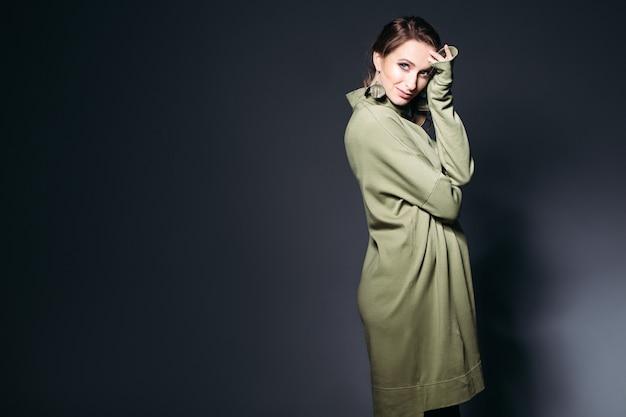 Mulher gravida elegante que levanta no estúdio escuro.