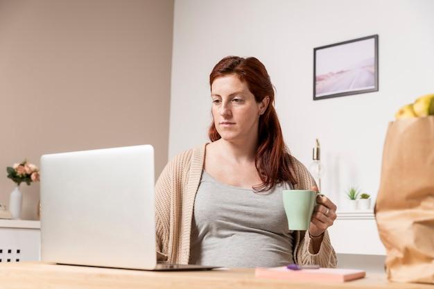 Mulher gravida em casa bebendo chá