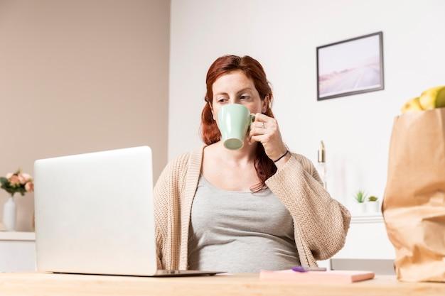 Mulher gravida em casa olhando no laptop