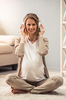 Mulher grávida em fones de ouvido está ouvindo música.