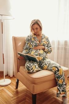 Mulher grávida em macacão com ornamento floral tocando a barriga e lendo um livro interessante enquanto relaxa em uma cadeira confortável em casa