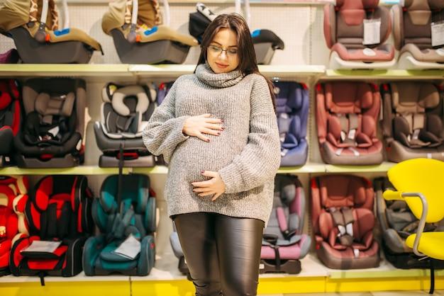 Mulher grávida em pé aganst prateleira com cadeiras de criança na loja. bens para o transporte seguro de crianças