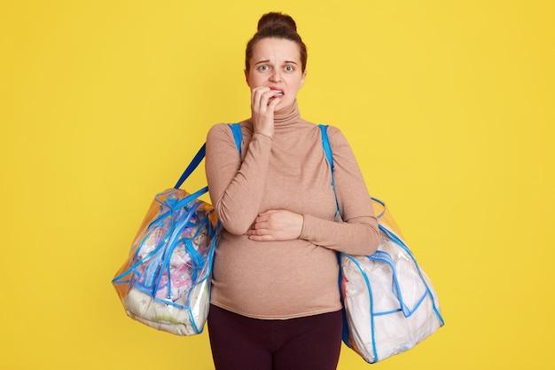 Mulher grávida em pé isolada na parede amarela pronta para dar à luz indo para o hospital, preocupada, parece assustada, mordendo os dedos, em pé com duas sacolas com coisas para futura mamãe e bebê
