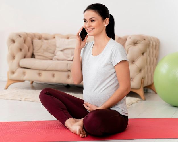 Mulher grávida em posição de lótus falando ao telefone